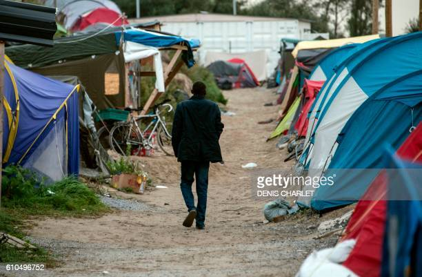 TOPSHOT A migrant walks on September 26 2016 in the socalled 'Jungle' migrant camp in the French northern port city of Calais French President said...