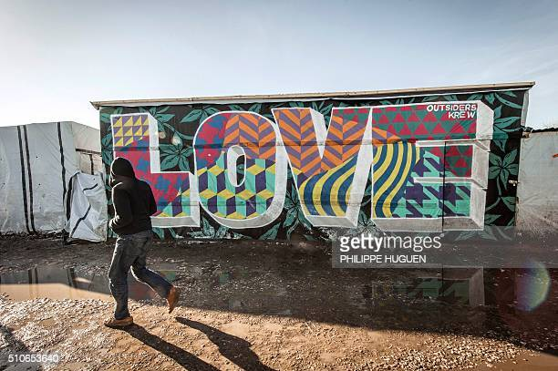 TOPSHOT A migrant walks past a mural with the lettering 'love' in the 'Jungle' camp in the port town of Calais northern France on February 16 2016...