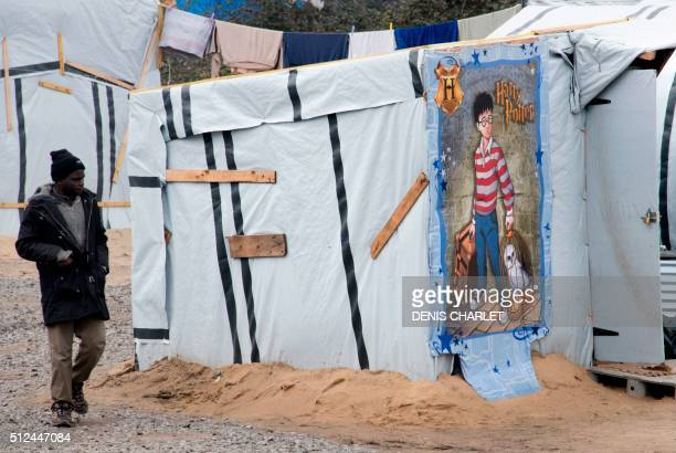 TOPSHOT A migrant walks past a shack made with a towel bearing the fictional character Harry Potter on February 26 2016 at the 'Jungle' migrants and...