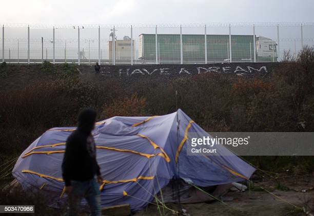 A migrant walks past a tent in front of writing on the ground saying 'We Have a Dream' in the camp known as 'The Jungle' on January 5 2016 in Calais...