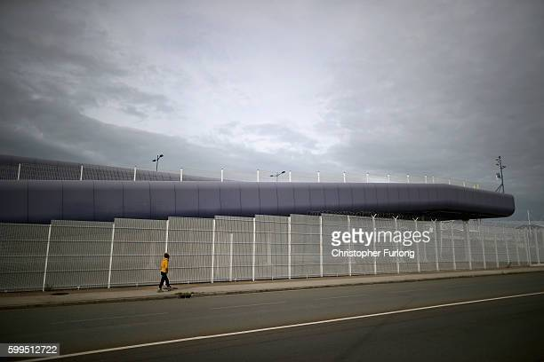 A migrant walks past security fencing surrounding the Port of Calais on September 5 2016 in Calais France Local people and business owners are taking...