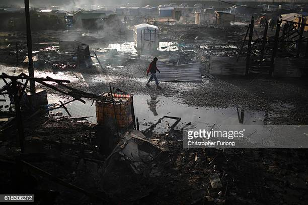 A migrant walks through the burnt out Jungle camp as authorities demolish the site on October 26 2016 in Calais France Overnight fires broke out in...
