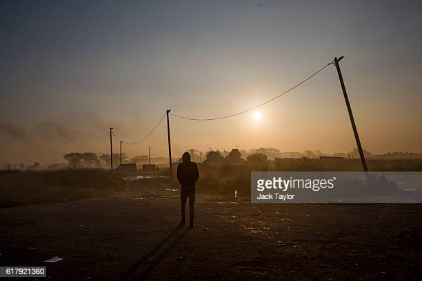 A migrant walks through the Jungle migrant camp as the sun rises over the makeshift Eritrean Church on October 25 2016 in Calais France Migrants are...