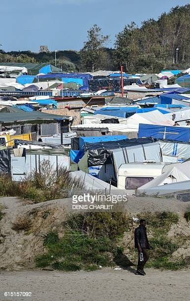 A migrant walks through the Jungle migrant encampment in Calais on October 17 before the dismantlement of the site Authorities have identified more...
