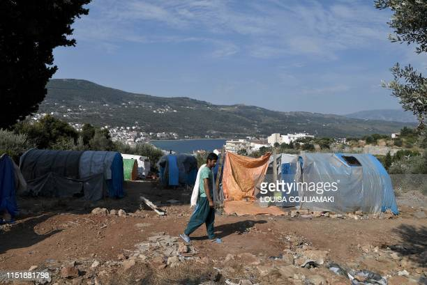A migrant walks to take a shower at the makeshift refugee camp above the city of Vathy on the island of Samos early on June 18 2019 Less than two...