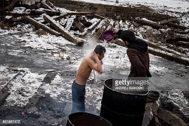 A migrant washes himself outside a derelict warehouse used as a shelter near Belgrade's main railway station on January 17 with temperatures bellow...