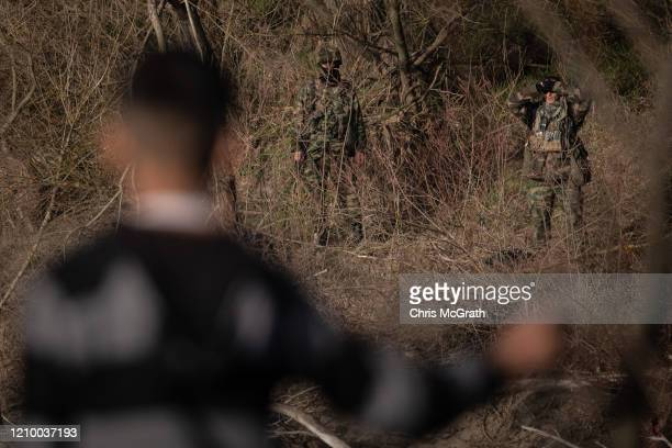 A migrant watches from the Turkish shoreline as Greek soldiers patrol the edge of the Evros river on March 03 2020 in Edirne Turkey Thousands of...