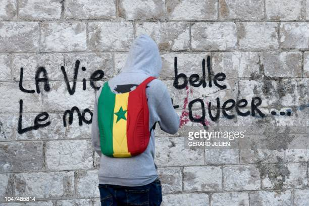 A migrant with a backpack with the colours of the Ghanaian flag passes near a tag The life is beautiful the world is queer during an operation by...