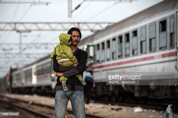 A migrant with a child stands near a train at the train station in Dugo Selo near Zagreb on September 17 2015 A special train transporting some 800...