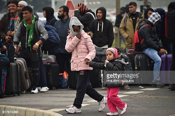 A migrant with her child walks past migrants who gather and wait with their luggage to leave the 'Jungle' migrant camp in Calais on October 24 2016...