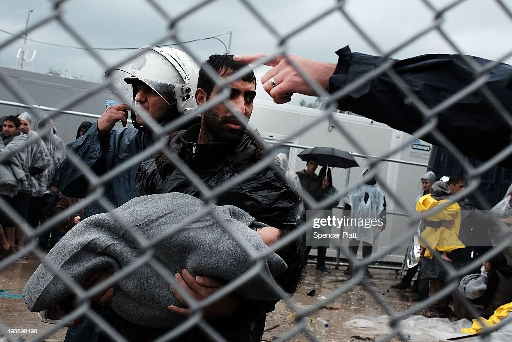 A migrant with his sick child is told to go away by the police at the increasingly overwhelmed Moria camp on the island of Lesbos on October 23, 2015 in Mitilini, Greece. Dozens of rafts and boats are still making the journey daily as thousands flee conflict in Iraq, Syria, Afghanistan and other countries. More than 500,000 migrants have entered Europe so far this year. Of that number four-fifths of have paid to be smuggled by sea to Greece from Turkey, the main transit route into the EU. Nearly all of those entering Greece on a boat from Turkey are from the war zones of Syria, Iraq and Afghanistan.