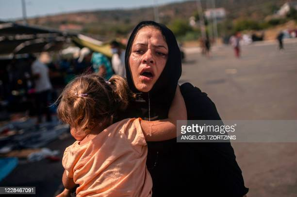 Migrant woman and a girl react after having been cleaned with water by another migrant after police threw tear gas during clashes near the city...