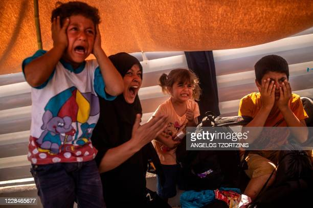 Migrant woman and children react after police threw tear gas during clashes near the city Mytilene on the Greek island of Lesbos, on September 12 a...