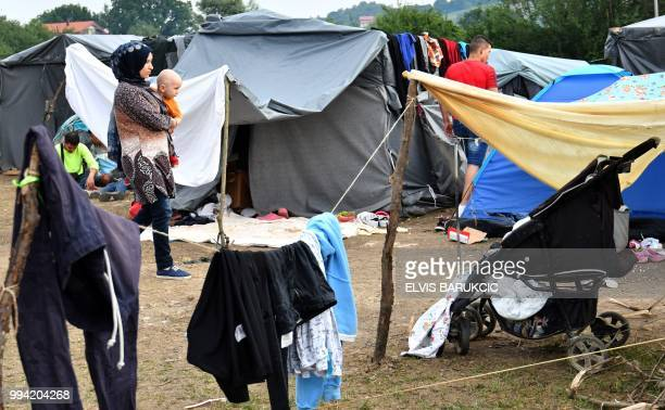 A migrant woman carries a child in a makeshift migrant camp outside the westernBosnian town of Velika Kladusa on July 3 2018