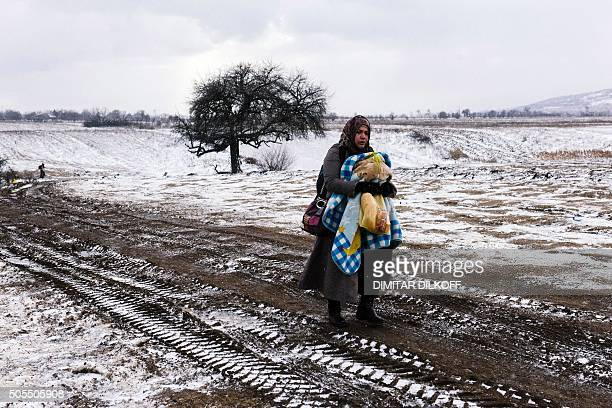 Migrant woman carries her baby as she walks through a snowy field, after crossing the Macedonian border into Serbia near the village of Miratovac on...