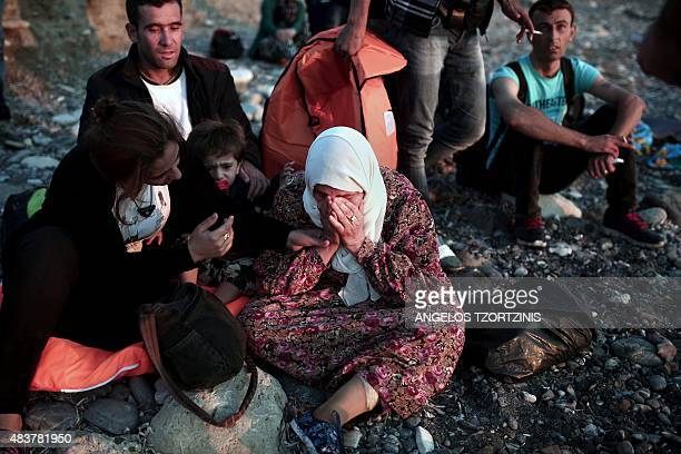A migrant woman cries upon reaching the Greek island of Kos after crossing a part of the Aegean Sea between Turkey and Greece on August 13 2015...