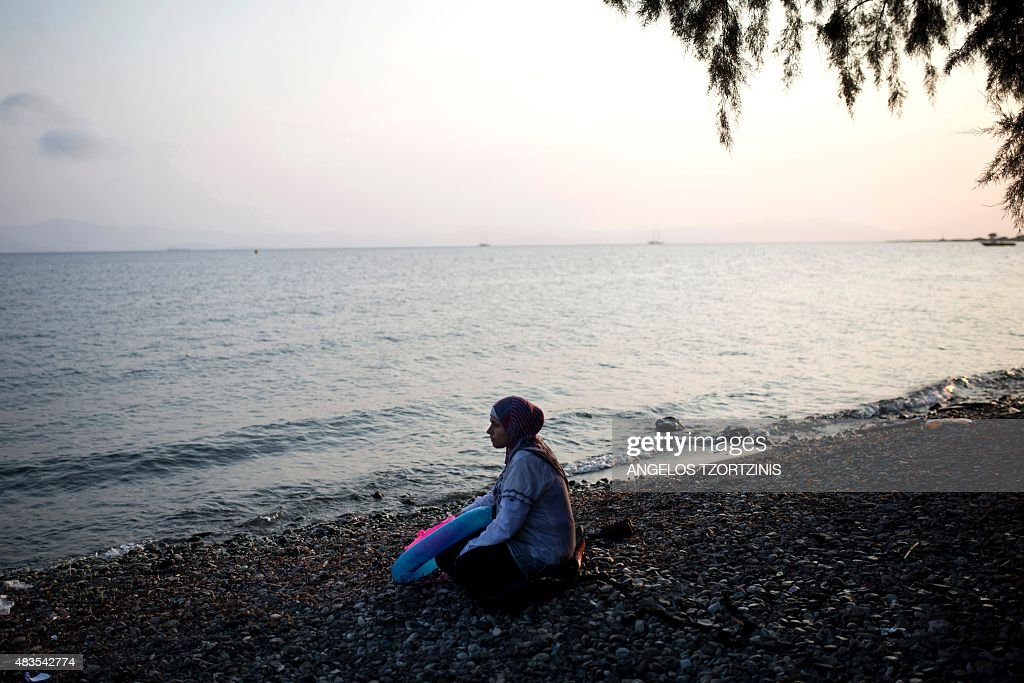 A migrant woman from Syria sits on a beach on the Greek island of Kos, after crossing a part of the Aegean Sea between Turkey and Greece, on August 10, 2015. The number of migrants and refugees arriving on Greece's shores has exploded this year, but the Mediterranean country provides virtually no reception facilities and leaves them wallowing in 'totally shameful' conditions, a UN official said on August 7. / AFP / ANGELOS