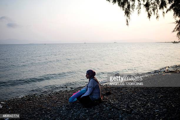 A migrant woman from Syria sits on a beach on the Greek island of Kos after crossing a part of the Aegean Sea between Turkey and Greece on August 10...