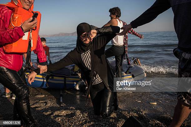 A migrant woman from Syria stumbles as she lands on shore after completing a journey in a small dinghy crossing a three mile stretch of the Aegean...