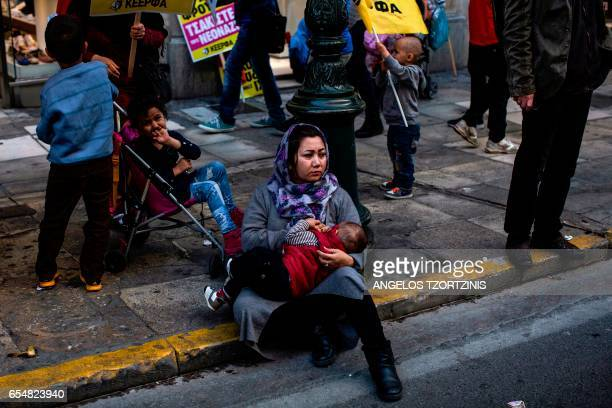 TOPSHOT A migrant woman holds a baby prior to a demonstration by Greek antifascist groups against the war in Syria and the European Union's stance on...