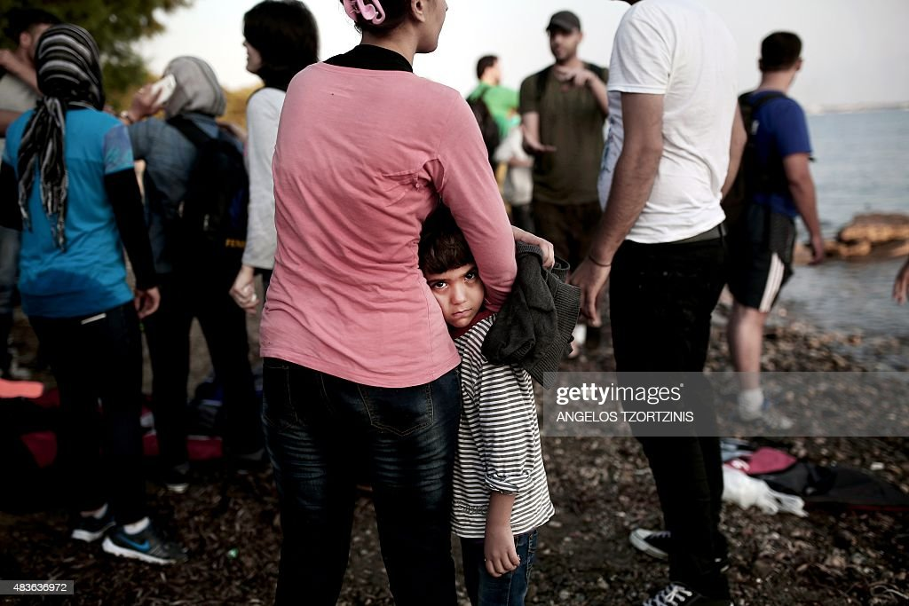 A migrant woman hugs her child after they arrived by boat on a beach on the Greek island of Kos, after crossing a part of the Aegean Sea between Turkey and Greece, on August 11, 2015. The number of migrants and refugees arriving on Greece's shores has exploded this year, but the Mediterranean country provides virtually no reception facilities and leaves them wallowing in 'totally shameful' conditions, a UN official said on August 7. / AFP / ANGELOS