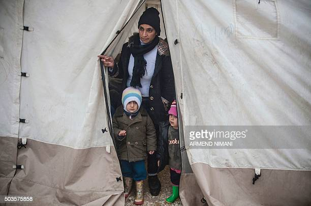 Migrant woman looks out of the tent with her children as they wait to board a bus with other migrants and refugees in southern Serbian town of...
