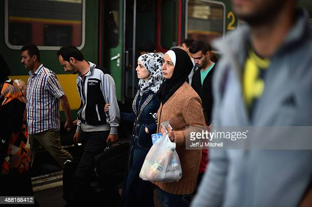 Migrant women look anxious as they make their way to board a train leaving for the Austrian border at the Keleti railway station on September 14 2015...