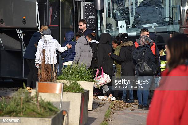 Migrant women queue to climb in a bus as they leave the Jules Ferry reception centre next to the recently demolished Jungle migrant camp after a...