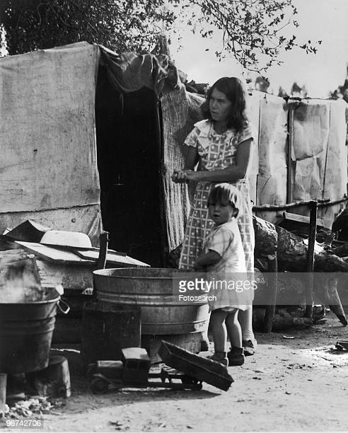 Migrant worker and child - photographed by Dorothea Lange - at a camp in Imperial Valley, California, circa 1935. .