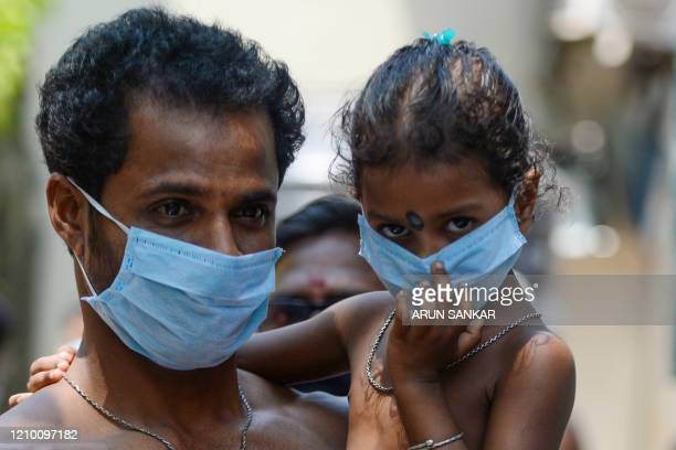 Migrant worker and his daughter wait to get food at a camp during a government-imposed nationwide lockdown as a preventive measure against the spread...