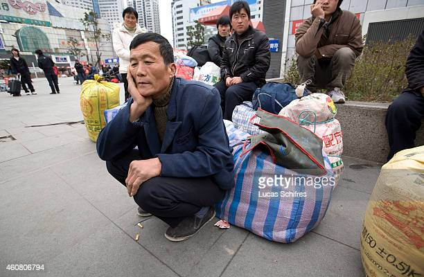 Migrant worker Bo Zhougao sits by his belongings near Shanghai train station on February 17 2009 in Shanghai China 50yearold Bo Zhougao has been...