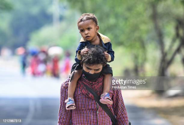 Migrant worker carries a child as he heads to his native state during lockdown, in Vasant Kunj, on May 13, 2020 in New Delhi, India.