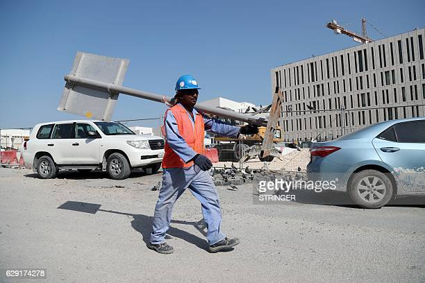 A migrant worker carries a pole at a construction site in the Qatari capital Doha on December 6 2016 Ever since being chosen as the 2022 World Cup...