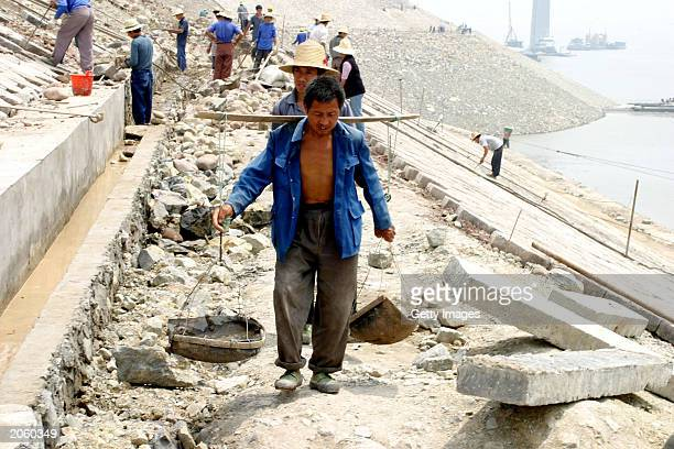 Migrant worker carries cement on poles at a dike construction site in the newly erected town of Fengjie to protect against the rising Yangzi river on...
