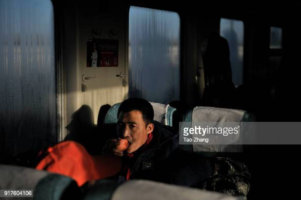 Migrant Worker eats apple at the original K48 train starting from Hangzhou and ending Qiqihar on 13 February 2018. Northeast China's Heilongjiang...