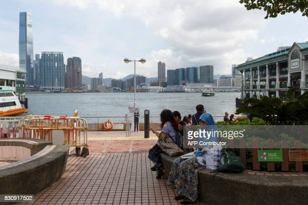 A migrant worker employed as a domestic maid speaks to a loved one via a video call on her smartphone on her day off at the Central ferry piers in...