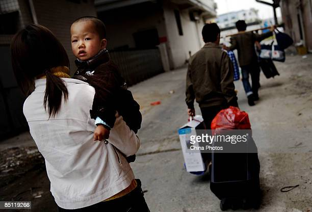 A migrant worker family prepares to return to their hometown after the jean factory where they worke closed down at the Dadun Village on February 20...