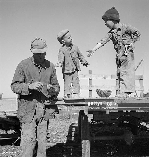 Migrant Worker Giving his Two Sons Watermelon, Dead Ox Flat, Malheur County, Oregon, USA, Dorothea Lange for Farm Security Administration, October...