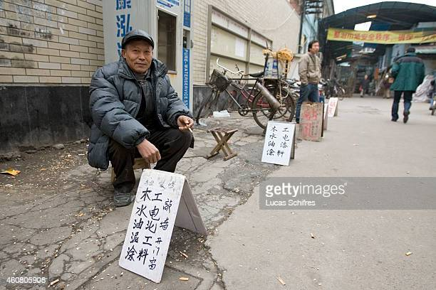 A migrant worker or 'mingong' from Jiangsu province looks for a day or coupleofhours' job by advertising on the sidewalk what he can do on February 3...
