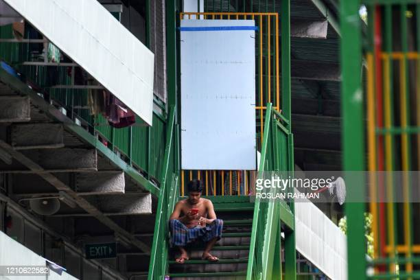 Migrant worker rest on the staircase after lunch break at the dormitories that houses foreign workers and has been made into an isolation area to...