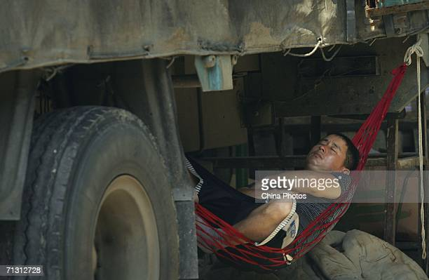 A migrant worker rests under a truck loaded with vegetables for sale at a wholesale market on June 26 2006 in Guangzhou of Guangdong Province China...