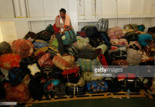 A migrant worker searches through piledup luggage after an evacuation trip from the besieged city of Misrata April 15 2011 in Benghazi Libya Nearly...