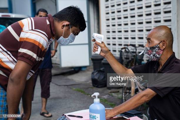 Migrant worker wearing protective face mask has his temperature checked by a security guard before leaving a factory-converted dormitory on April 17,...