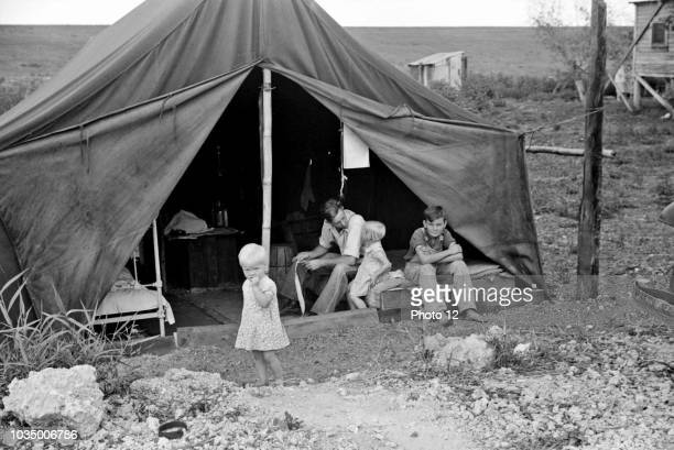 Migrant worker with his children living in a tent during the American Great Depression.