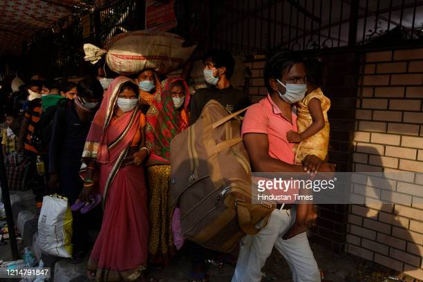 Migrant workers along with their families stand in a queue for thermal screening at Govt Sarvodaya Kanya Bal Vidyalaya West Vinod Nagar before being...