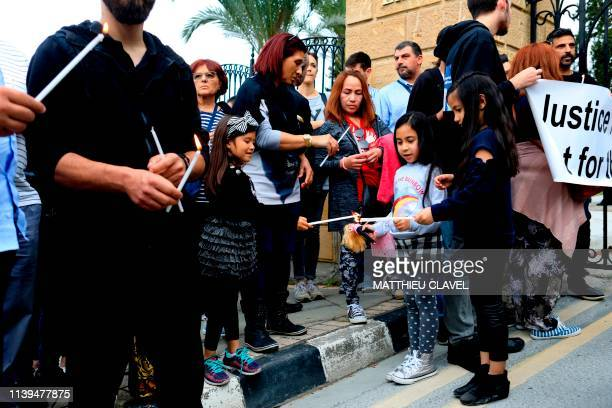 Migrant workers and children light candles as protesters demonstrate in support of the victims of a suspected serial killer in front of the...