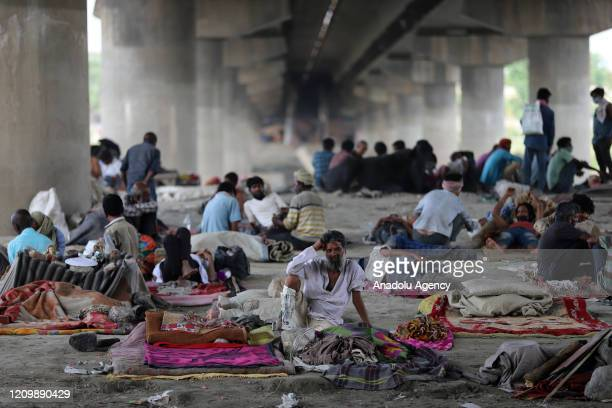 Migrant workers and homeless people take refuge under a bridge on the banks of the Yamuna River during a 21-day nationwide lockdown to slow the...