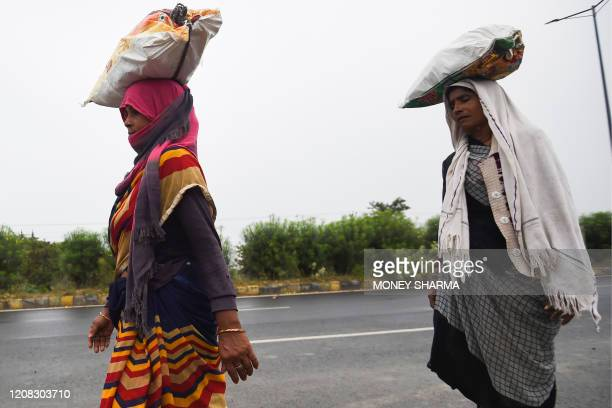 Migrant workers and their family members walk with their belongings on a highway towards Uttar Pradesh as they leave for their villages during a...