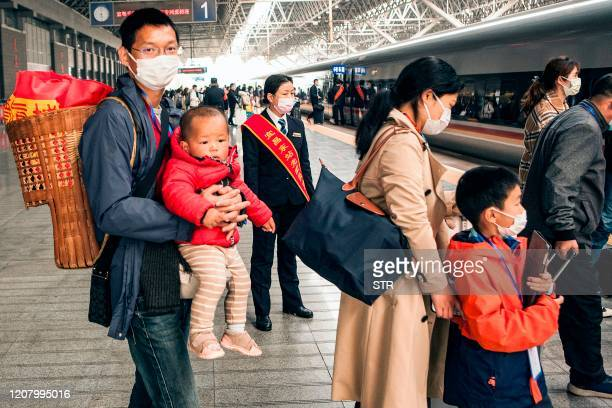 Migrant workers and their relatives queue as they prepare to get on a special train before departing to Shenzhen in Yichang in China's central Hubei...