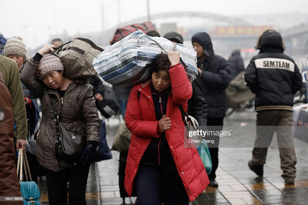 Migrant workers arrive at the Beijing Railway Station with their luggage on January 31, 2013 in Beijing, China. The Spring Festival travel season runs from January 26 to March 6 and according to reports road passenger transport in China is estimated at 3.1 billion people during this time of year.